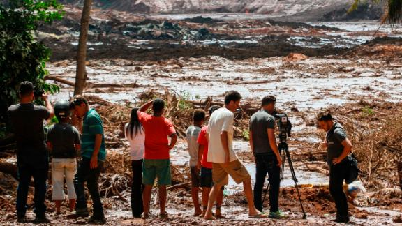25 January 2019, Brazil, Brumadinho: People observe the mud masses after the break of a dam at the Feij