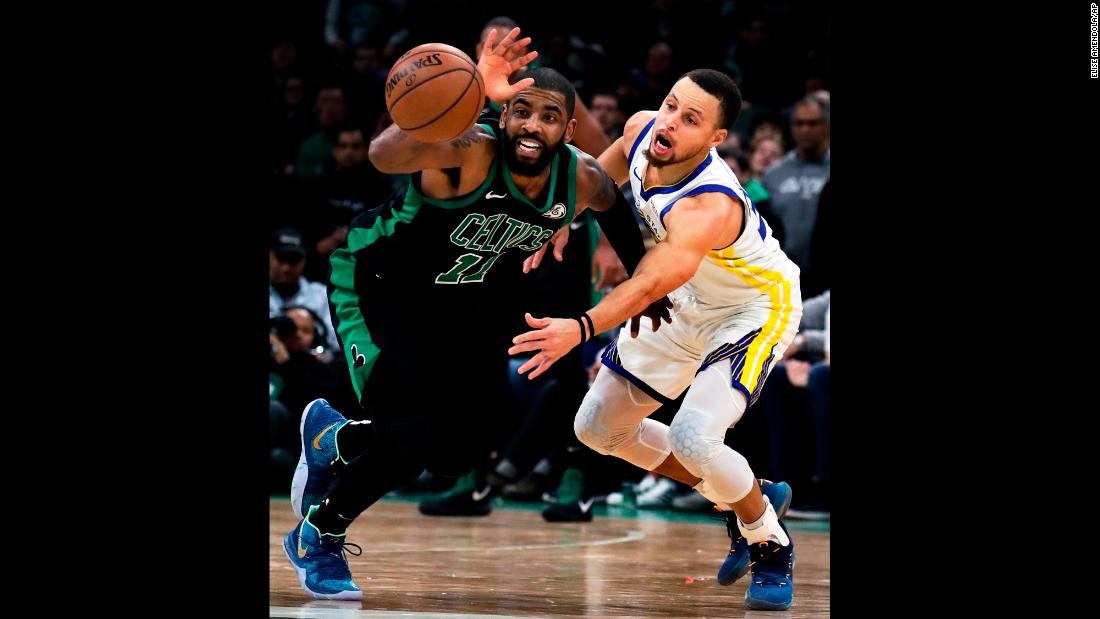 Golden State's Stephen Curry, right, tries to steal the ball from Boston's Kyrie Irving during an NBA game in Boston on Saturday, January 26.