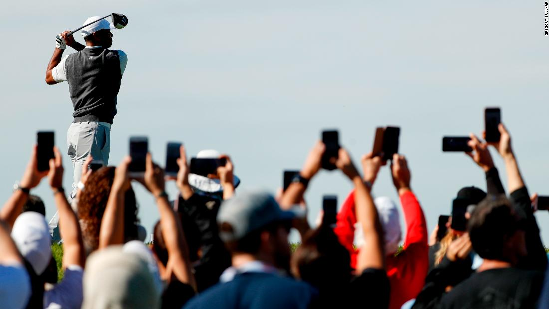 Golf fans get a shot of Tiger Woods' tee shot during the first round of the Farmers Insurance Open on Thursday, January 24.