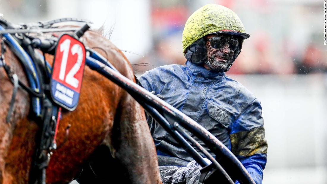 Jean-Michel Bazire is covered in mud during a harness race in Paris on Sunday, January 27.