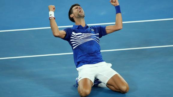 Novak Djokovic sinks to the court after beating Rafael Nadal at the Australian Open.