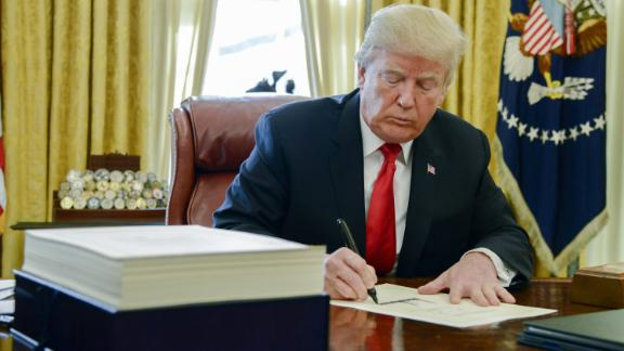 U.S. President Donald Trump signs a tax-overhaul bill into law in the Oval Office of the White House in Washington, D.C., U.S., on Friday, Dec. 22, 2017. This week House Republicans passed the most extensive rewrite of the U.S. tax code in more than 30 years, hours after the Senate passed the legislation, handing Trump his first major legislative victory providing a permanent tax cut for corporations and shorter-term relief for individuals. Photographer: Mike Theiler/Pool via Bloomberg