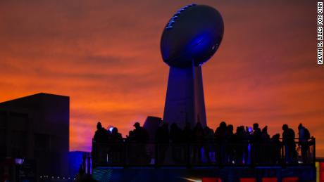 The sun sets over Super Bowl LIVE and a giant version of the Lombardi Trophy in Centennial Park on Sunday, January 27, 2018. Photo by Kevin D. Liles for CNN