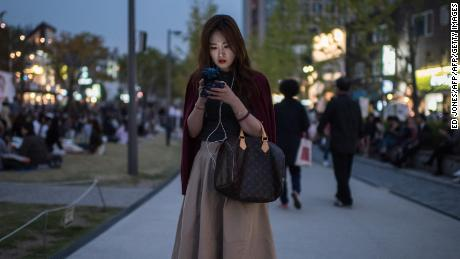 A woman looks at a mobile phone as she stands on a path in the popular Yeonnam-dong area of Seoul on October 15, 2016. / AFP / Ed Jones        (Photo credit should read ED JONES/AFP/Getty Images)