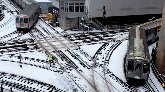 Chicago's L trains move along snow-covered tracks Monday.