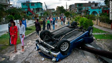 Havana pedestrians pass an overturned vehicle on Monday.