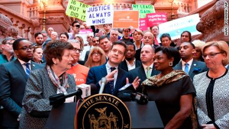 New York Sen. Brad Hoylman, center, flanked by former Assemblywoman Margaret Markey, left, and Senate Majority Leader Andrea Stewart-Cousins, right, join survivors and advocates speaking in favor of the legislation.