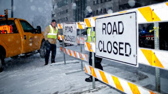 City workers put up a road closed sign on the Michigan Street hill in Grand Rapids, Mich., Monday, Jan. 28, 2019. Snow made travel dangerous is many areas of the state. Heavy snow and gusting winds created blizzard-like conditions Monday across parts of the Midwest, prompting officials to close hundreds of schools, courthouses and businesses, and ground air travel. (Neil Blake/The Grand Rapids Press via AP)
