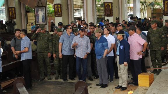 Philippine President Rodrigo Duterte accompanied by Defense Secretary Delfin Lorenzana inspect the damaged area of the church in Jolo.