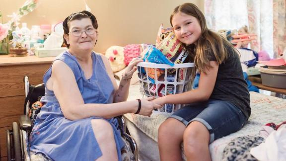 """Ruby Kate Chitsey delivers a nursing home resident some of the items requested through """"Three Wishes."""""""