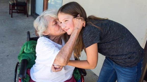 11-year-old Ruby Kate Chitsey gets kisses from a nursing home resident.