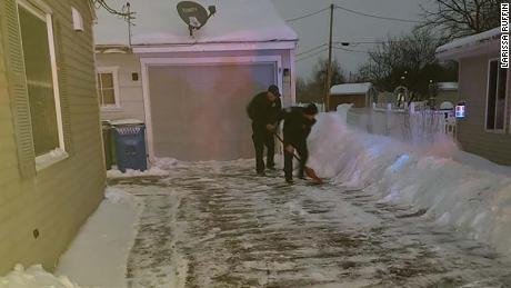 Iowa firefighters who were called to a home delivery shovel snow from the new parents' driveway.