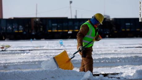 A worker shoveling snow on the rails of the Metra Western Avenue Yard in Chicago.