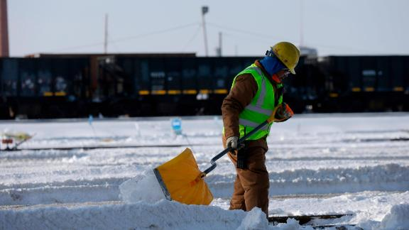 A worker shovels snow off the rail switches at the Metra Western Avenue Yard in Chicago.