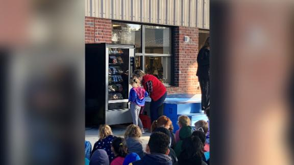 A student uses the book vending machine for the first time.