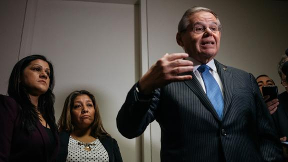 Sandra Diaz, left, and Victorina Morales stand by as Sen. Bob Menendez delivers remarks to reporters.