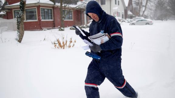 A Postal Service carrier delivers mail Monday in East Grand Rapids, Michigan. East Grand Rapids is one of the ares where mail service was suspended Wednesday.