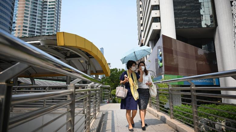 People wearing face masks walk on a bridge in Bangkok's central business district.