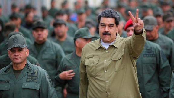 "In this handout photo released by the Miraflores Presidential Press Office, Maduro flashes a ""V for victory"" hand gesture after arriving at the Fort Tiuna military base in Caracas on January 30."