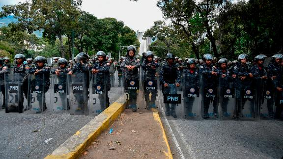 Members of the National Police line up to guard the entrance of Venezuela