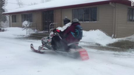 Pharmacist Andrea Cusack makes deliveries via a snowmobile, one of this week's acts of generosity.