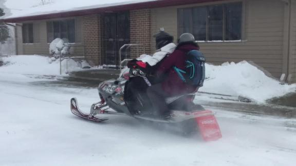 A Michigan pharmacist jumped on a snowmobile to deliver medicine to customers.