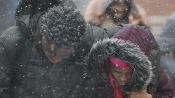 Pedestrians duck the wind as they  walk through heavy snow in Manhattan on Wednesday.