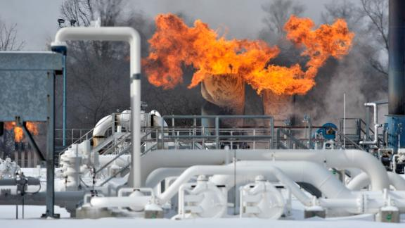 Fire comes out of the top of two silo-looking structures at the compressor station at Consumers Energy in Armada Township, Mich.  Consumers Energy has called on customers to voluntarily reduce their natural gas usage following a fire at a suburban Detroit gas compressor station amid bitterly cold weather. The Jackson-based utility says no one was injured in the fire Wednesday, Jan. 30, 2019, at its Ray Natural Gas Compressor Station in Macomb County. The cause of the fire was under investigation. (Todd McInturf/Detroit News via AP)