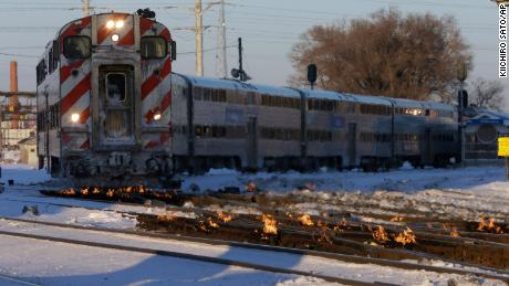 A train travels in Chicago as a gas-fired switch heater on the rails keeps the ice and snow off switches.