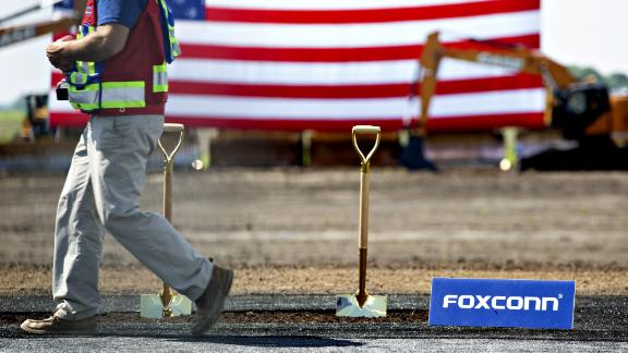 A worker walks past shovels in a patch of dirt ahead of the groundbreaking ceremony for the Foxconn Technology Group facility in Mount Pleasant, Wisconsin, U.S., on Thursday, June 28, 2018. After repeatedly bashing the leadership of Harley-Davidson Inc. this week, President Donald Trump is set to be 30 miles away from its corporate headquarters during the groundbreaking for the Foxconn Technology Group electronic screen manufacturing campus. Photographer: Daniel Acker/Bloomberg via Getty Images