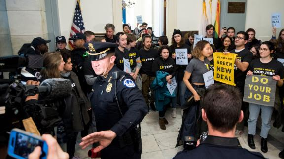 UNITED STATES - DECEMBER 10: Capitol Police move press and protesters back as protesters with the Sunrise Movement protest in House Minority Leader Nancy Pelosi's office in the Cannon House Office Building demanding a clim ate deal from Democrats on Monday, Dec. 10, 2018. (Photo By Bill Clark/CQ Roll Call) (CQ Roll Call via AP Images)