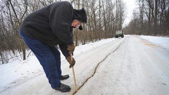 In a Saturday, Jan. 11, 2014 photo, Dennis Olsen measures a giant fissure, which he measured to be an inch wide and at least eight to ten inches deep, in his rural driveway in Waupun, Wis., after a weather phenomenon known as an ice quake occured recently. It results from water freezing and expanding in the soil and bedrock. (AP Photo/The Reporter, Aileen Andrews) NO SALES