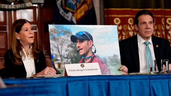 Linda Beigel Schulman, left, holds a photograph of her son Scott Beigel, who was killed by gun violence while speaking with New York Gov. Andrew Cuomo and gun safety advocates in the Red Room during a news conference at the state Capitol on Tuesday, Jan. 29, 2019, in Albany, N.Y. (AP Photo/Hans Pennink)