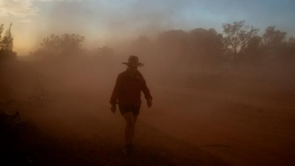 An Australian farmer walks through a cloud of dust on her property on January 16.
