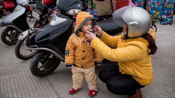 """ZHAOQING, CHINA - JANUARY 25: (CHINA OUT) A mother feeds their child porridge at a gas station after riding their motorcycle on January 25, 2019 in Zhaoqing, Guangdong Province, China. The Motorcycle Return League refers to the migrant workers who ride motorcycles back home together. Many migrant workers in Guangdong choose this way to go home for the Spring Festival and the Chinese media call these people the """"Motorcycle Army"""", which started at the Spring Festival of 2000. In the Spring Festival of 2014, the flow of motorcycles returning home increased dramatically with more than 600,000 migrant workers chosing to ride motorcycles back to their homes in Guangxi, Guizhou and other provinces and regions. With the development of high-speed railways and the popularization of private cars, the number of motorcycle riders has dropped sharply for the Spring Festival of 2019. (Photo by Wang He/Getty Images)"""