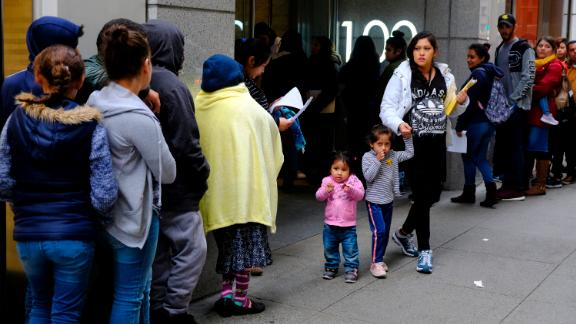 Hundreds of people overflow onto the sidewalk in a line snaking around the block outside a U.S. immigration office with numerous courtrooms Thursday, Jan. 31, 2019, in San Francisco. The crowd was mixed with people who had court appointments for Thursday, people whose appointments were swallowed up by shutdown and others who had