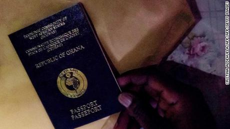 A man holds a Ghanaian passport.