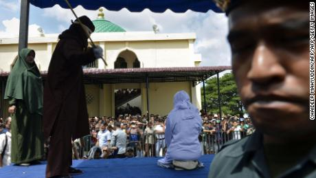 An Indonesian teen is caned in public in Banda Aceh as punishment for being caught cuddling with her boyfriend.
