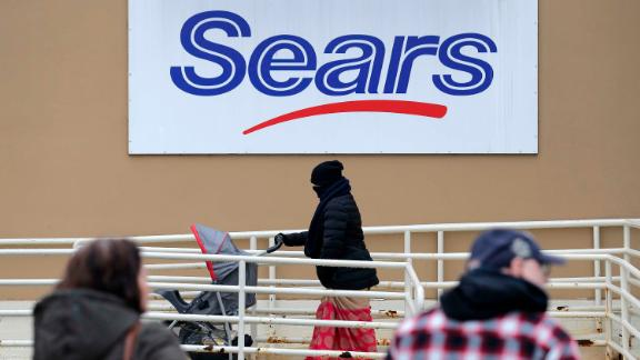 A person walks near a sign for a Sears store in Hackensack, N.J., Tuesday, Jan. 8, 2019. Sears is getting another reprieve from liquidation after its chairman and largest shareholder revised his bid to save the iconic brand, according to a hearing  Tuesday at the bankruptcy court in White Plains, N.Y. (AP Photo/Seth Wenig)