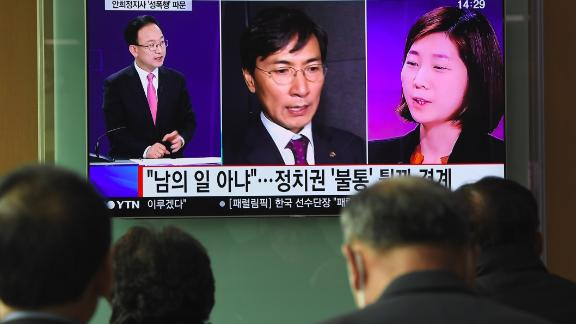People watch a television news report showing a picture of Kim Ji-eun (right on television), a secretary of Ahn Hee-jung, at a railway station in Seoul on March 6, 2018.