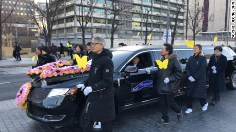 A car carrying Kim Bok-dong's casket drives through downtown Seoul.