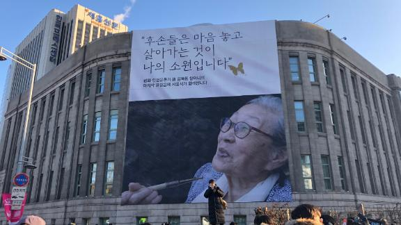 """A poster erected on the side of the Seoul Library, bearing a quote from Kim Bok-dong: """"My hope is that descendants live at ease."""""""