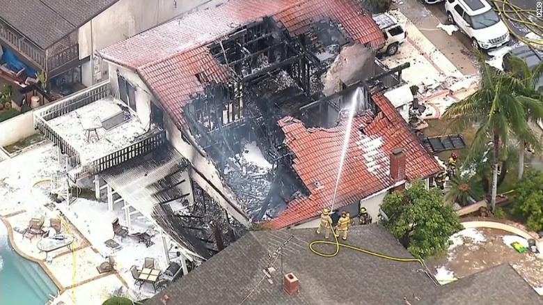 Firefighters work where a plane crashed into a home in Yorba Linda, California.