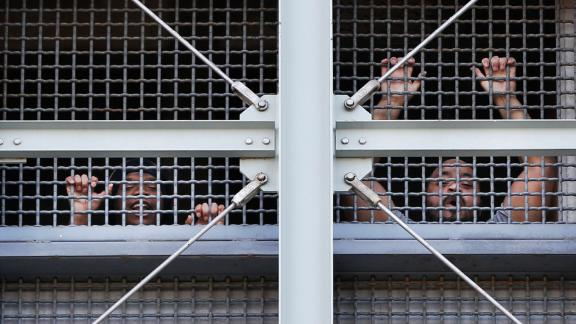 Prisoners call out to protesters and family members gathered outside the Metropolitan Detention Center on Sunday.