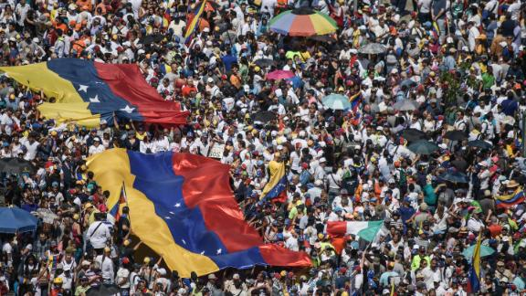 Guaido supporters hold huge Venezuelan flags during a protest against Maduro on Saturday.