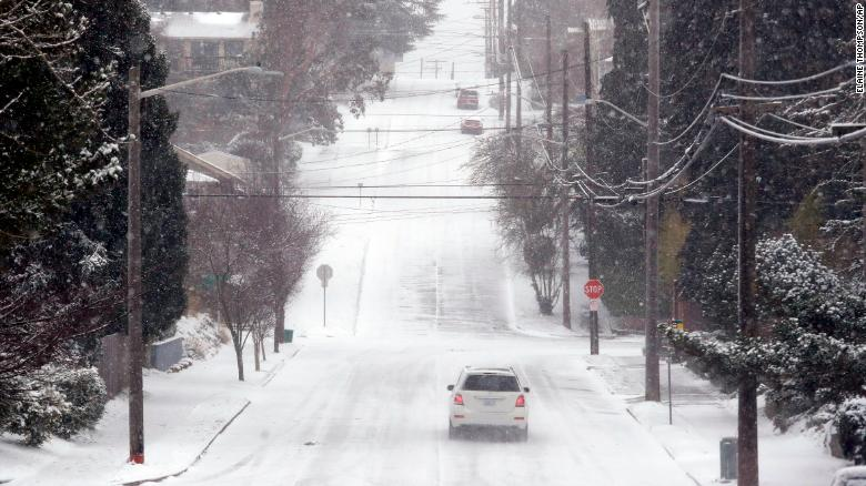 A lone car finds its way along an otherwise deserted street through snow and a cold wind Monday morning in Seattle.