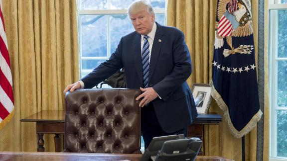 US President Donald Trump stands behind his desk after Jeff Sessions was sworn in as Attorney General in the Oval Office of the White House in Washington, DC, February 9, 2017. / AFP PHOTO / SAUL LOEB        (Photo credit should read SAUL LOEB/AFP/Getty Images)