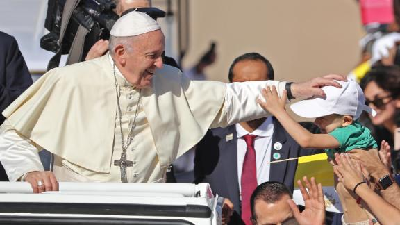 Francis blesses a child as he arrives at Tuesday