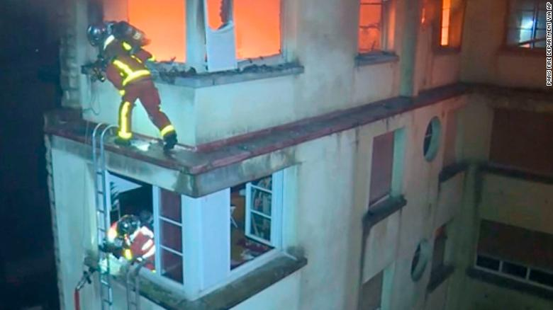 Firemen scale the top floors of the burning building.