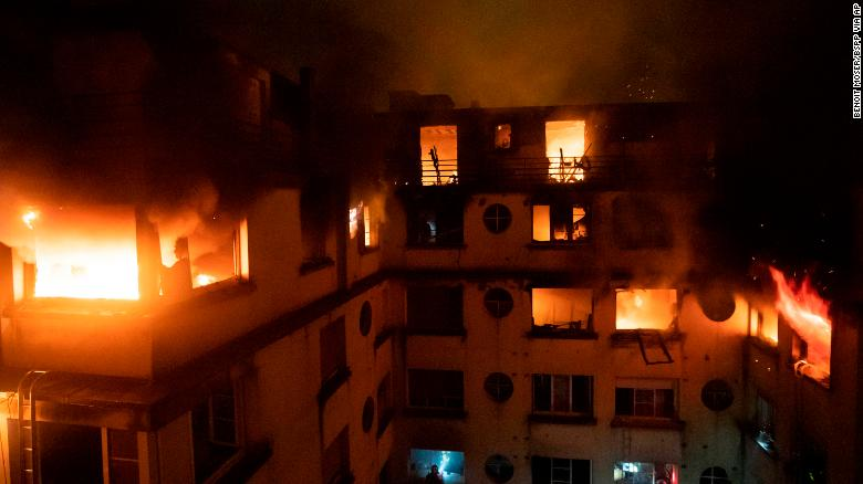 A fire rages through the top floors of an apartment building in Paris, France